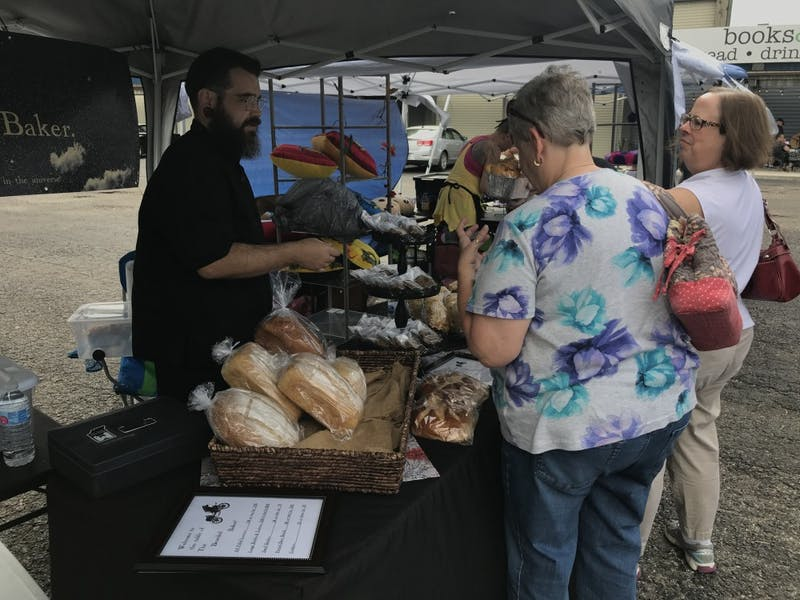 "Shane Heath shows his bread options to customers Saturday, Sept. 8, 2018 in Muncie, IN. Heath, known as the Bearded Baker, made his goods 24 hours before the event to ""ensure freshness."" Trevor Weldy, DN"
