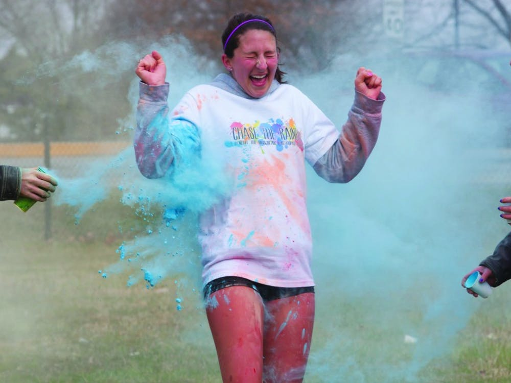 A runner reacts to getting hit with a colored substance during the Chase the Rainbow 5K race. DN PHOTO TAYLOR IRBY