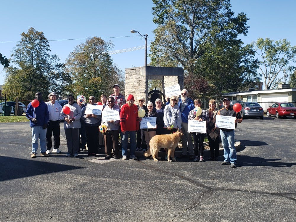 Participants hold up signs before participating in the walk. On Oct. 13 Christian Ministries held a hunger walk to help raise funds for their food pantry. Jaden Hasse, DN.