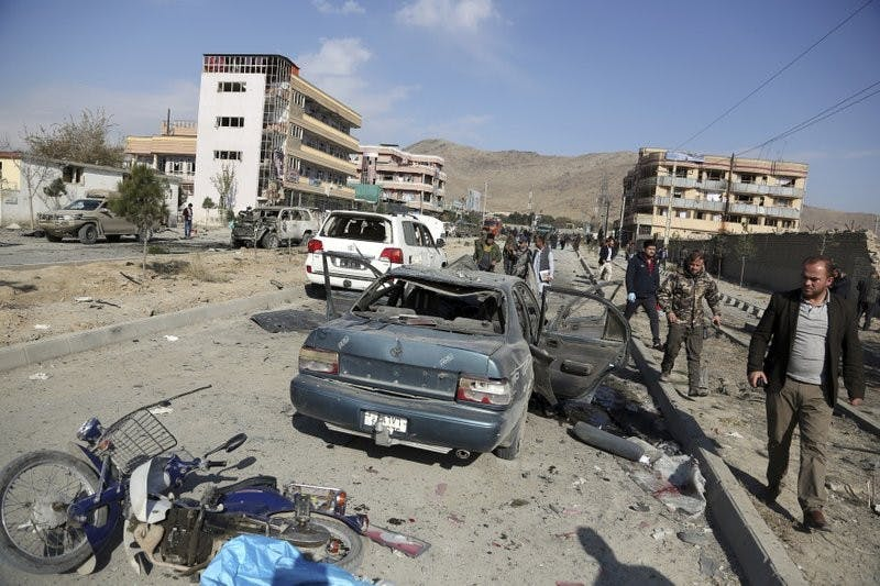 In this Nov. 13, 2019, file photo, Afghan security personnel gather at the site of a car bomb attack in Kabul, Afghanistan. Afghanistan will need vast amounts of foreign funding to keep its government afloat through 2024, a U.S. agency said Thursday, even as foreign donors are increasingly angry over the cost of debilitating corruption and the U.S. seeks a peace deal with Taliban to withdraw its troops. (AP Photo/Rahmat Gul, File)