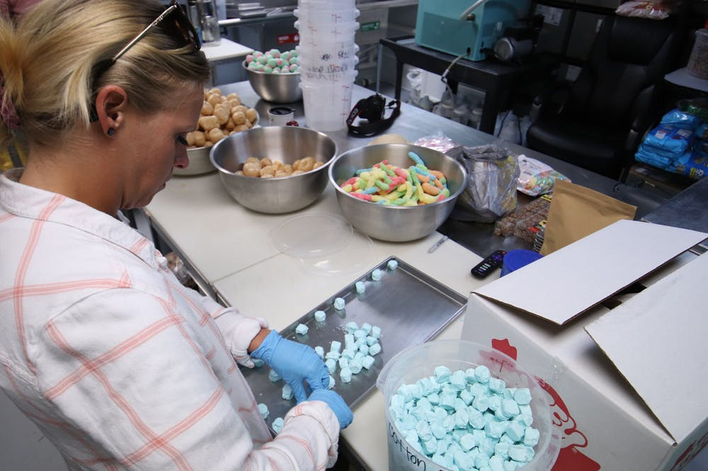<p>Mckensie Dishman, an employee of Fresh Market Treats, lays out pieces of saltwater taffy before placing them into the shop&#x27;s freeze dryer March 5, 2021. Rylan Capper DN </p>