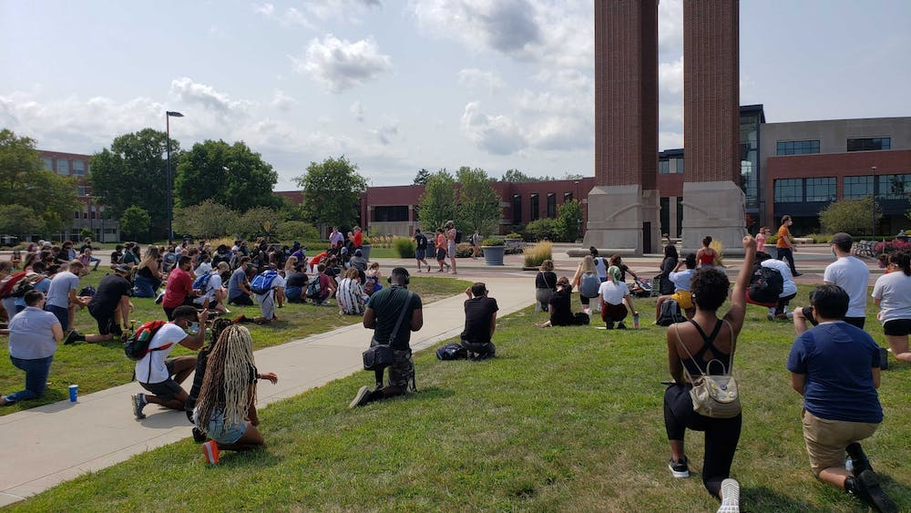 <p>Demonstrators kneel for 8 minutes and 42 seconds in memory of George Floyd at the University Green Tuesday Afternoon. The protest, which was organized by Ball State senior public communications major Taylor Hall, was attended by nearly 100 protesters.<strong> John Lynch, DN</strong></p>