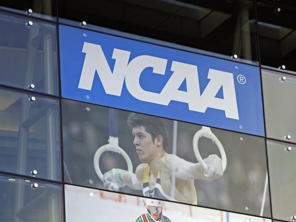 In this April 25, 2018, file photo, the NCAA headquarters is shown in Indianapolis. The NCAA is expected to approve a recommendation to all athletes who compete in fall sports, including football, over the next 10 months to not be charged a year of eligibility. It's great news for current players, but comes with some complications for teams, coaches and future college football players. (AP Photo/Darron Cummings, File)