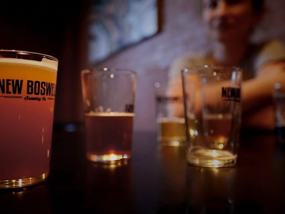 Three customers drink at New Boswell Brewery Company in Richmond, Ind., during the filming of