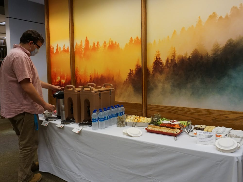 A visitor fills a cup with coffee at Bracken Library'snewly-opened contemplation space Sept. 29, 2021. The opening of the area was celebrated with snacks and speeches from universityfaculty. Hannah Amos, DN