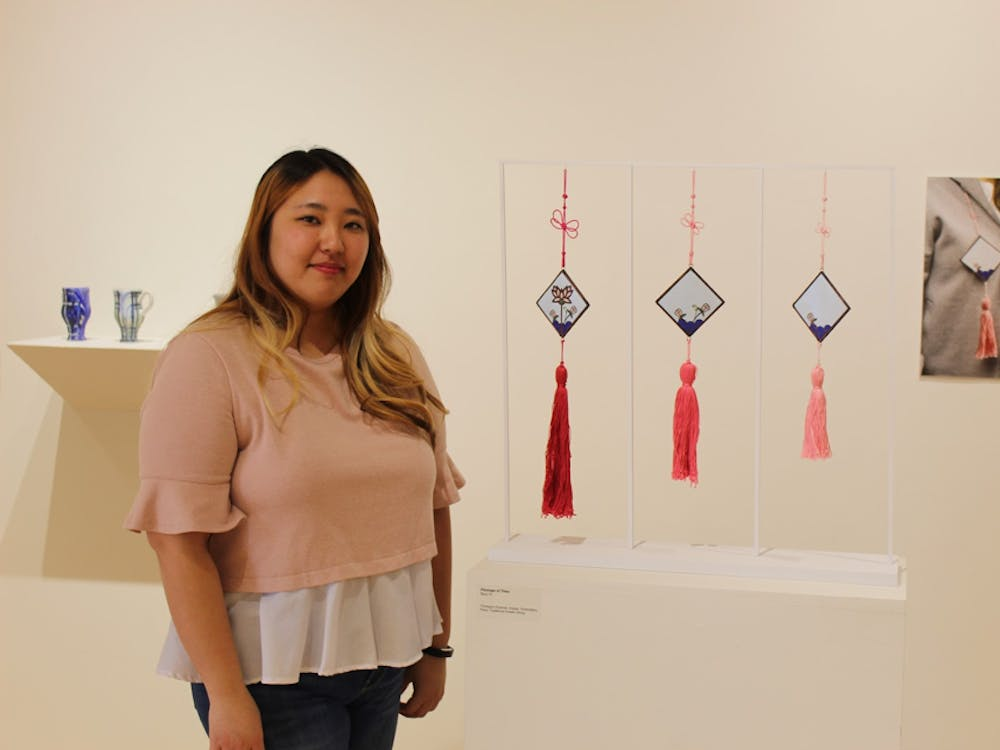 "Seul Yi in front of her work titled ""Passage of Time."" Her work is modeled after traditional Korean outfit tassels. The length of each resembles the passing of time. Chase Martin, DN"