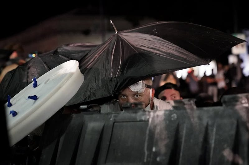A protester takes cover during clashes outside the Kenosha County Courthouse late Tuesday, Aug. 25, 2020, in Kenosha, Wis., during a third night of unrest following the shooting of a Black man whose attorney said he was paralyzed after being shot multiple times by police. (AP Photo/David Goldman)