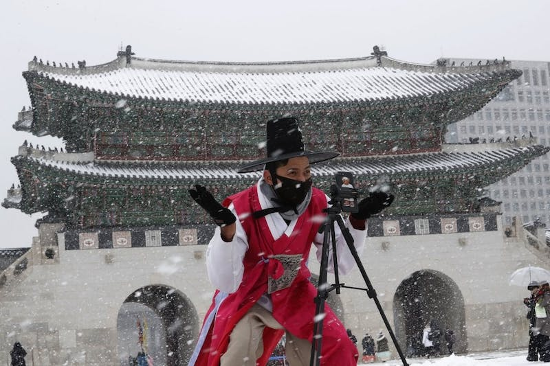 """A man dressed in South Korean traditional """"Hanbok"""" attire wears a face mask in the snow as he gestures to take photos Feb. 17, 2020, at the Gyeongbok Palace, the main royal palace during the Joseon Dynasty in Seoul, South Korea. Chinese authorities on Monday reported a slight upturn in new virus cases and hundred more deaths for a total of thousands since the outbreak began two months ago. (AP Photo/Ahn Young-joon)"""