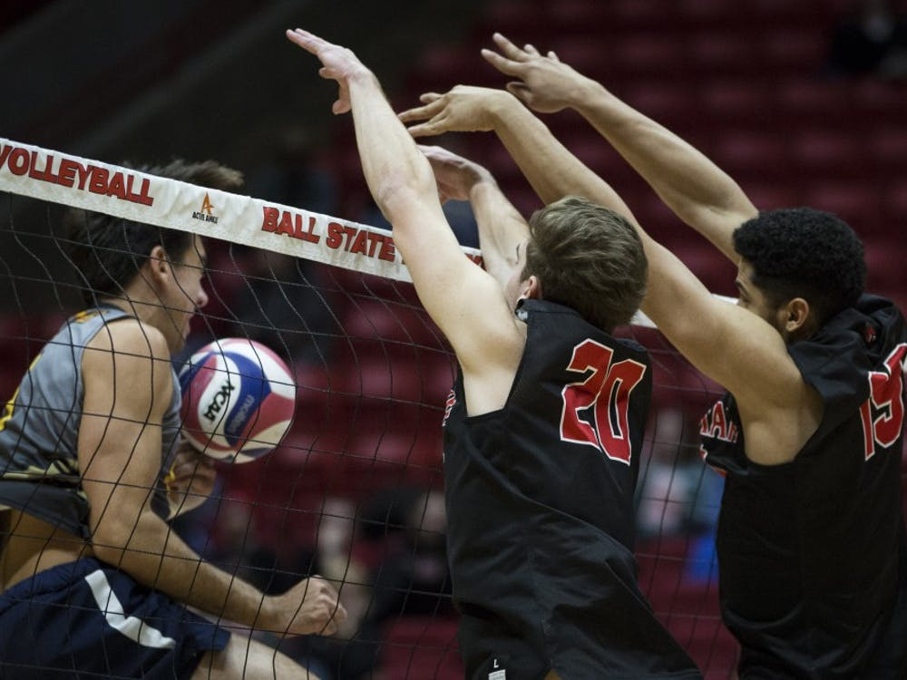 Junior outside hitter David Siebum and red shirted sophomore middle attacker Lem Turner pushes a kill back over the net against a Emmanuel Lions attacker, Jan. 6, at John E. Worthen Arena. Ball State swept the Lions, in three straight sets, 16-25, 15-25, 12-25. Grace Hollars, DN