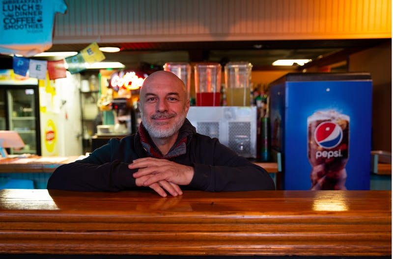 Basam Helwani, the owner of Two Cats Cafe and Damask Cafe, stands in Two Cats Wednesday, Dec. 4. He is closing down his restaurants after accepting an offer to work for Pocket Points in California. Brynn Mechem, DN Photo