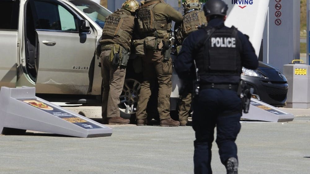 Royal Canadian Mounted Police officers surround a suspect at a gas station in Enfield, Nova Scotia on Sunday April 19, 2020. Canadian police say multiple people are dead plus the suspect after a shooting rampage across the province of Nova Scotia. (Tim Krochak/The Canadian Press via AP)