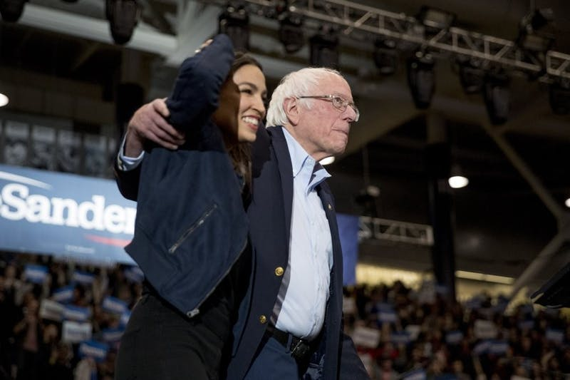 Democratic presidential candidate Sen. Bernie Sanders, I-Vt., accompanied by Rep. Alexandria Ocasio-Cortez, D-N.Y., left, takes the stage at campaign stop at the Whittemore Center Arena at the University of New Hampshire, Feb. 10, 2020, in Durham, N.H. (AP Photo/Andrew Harnik)