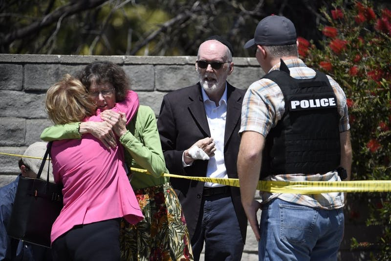 Two people hug as another talks to a San Diego County Sheriff's deputy outside of the Chabad of Poway synagogue, Saturday, April 27, 2019, in Poway, Calif. A man opened fire inside the synagogue near San Diego as worshippers celebrated the last day of a major Jewish holiday. (AP Photo/Denis Poroy)