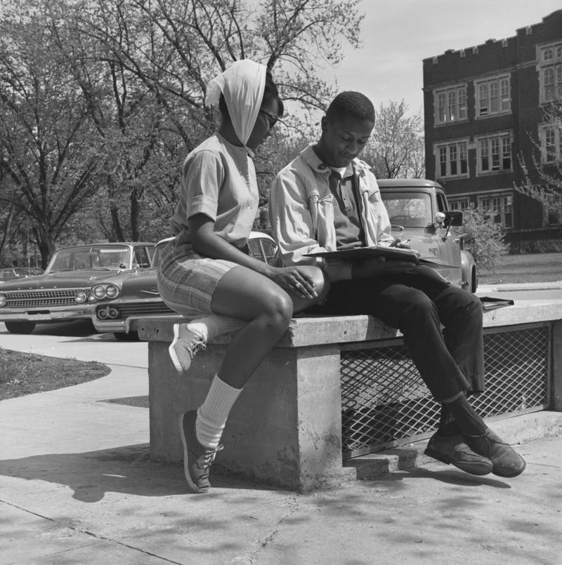 Two students read on a bench along a circular drive near the Administration Building in 1963 in Muncie, IN. Photo provided, Michael Szajewski.