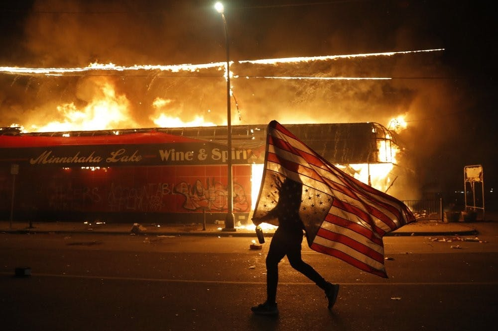 <p>A protester carries a U.S. flag upside, a sign of distress, next to a burning building Thursday, May 28, 2020, in Minneapolis. Protests over the death of George Floyd, a black man who died in police custody Monday, broke out in Minneapolis for a third straight night. <strong>(AP Photo/Julio Cortez)</strong></p>
