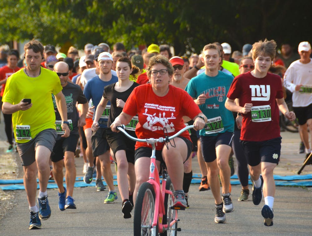 <p>A pacer on a bicycle leads the pack of runners at a previous Cardinal Greenways 5K. For 2021, Cardinal Greenways is hosting joint races in Muncie and Marion County. <strong>Brian Schleeper/ Cardinal Greenways, Photo Provided</strong></p><p></p>