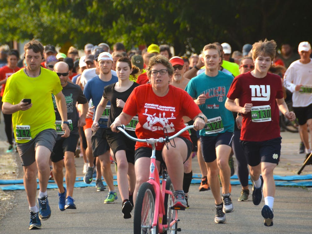A pacer on a bicycle leads the pack of runners at a previous Cardinal Greenways 5K. For 2021, Cardinal Greenways is hosting joint races in Muncie and Marion County. Brian Schleeper/ Cardinal Greenways, Photo Provided