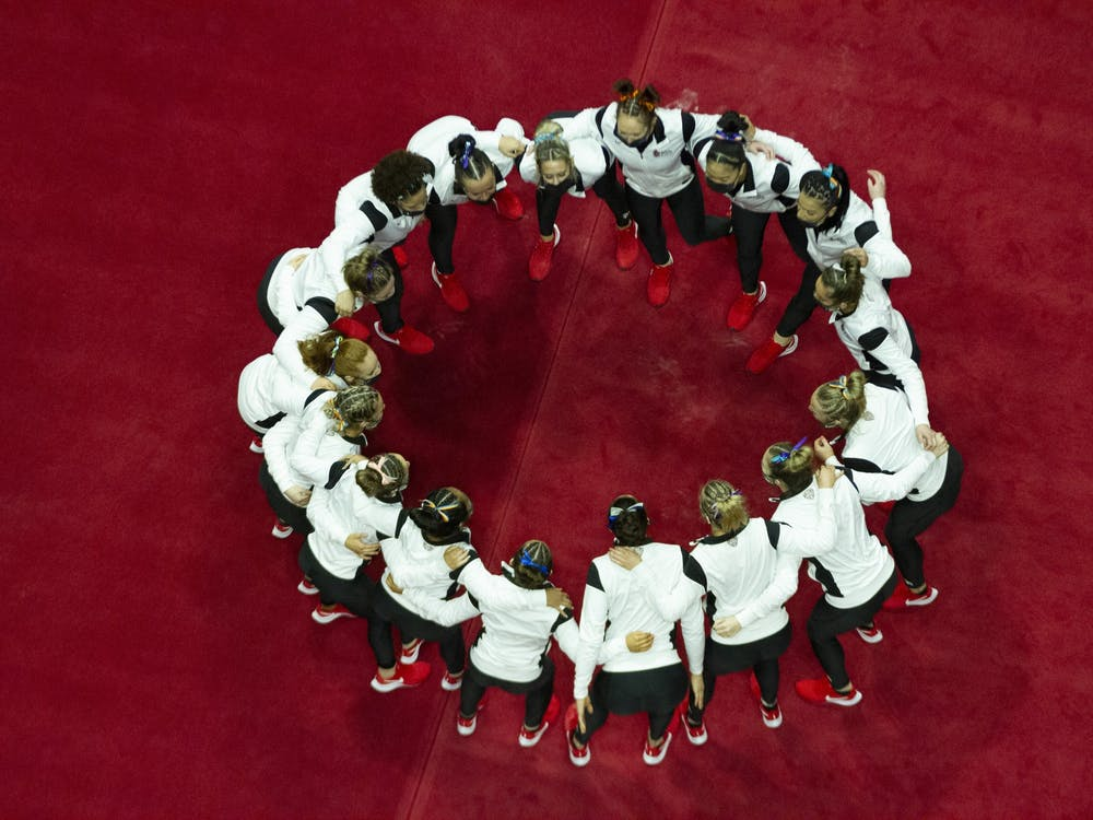 The gymnastics team huddles up for one last time as a team on Senior Day Feb. 28, 2021, at John E. Worthen Arena. The Cardinals lost their first meet this season in a 194.300-194.225 loss the the Western Michigan Broncos. Grace Walton, DN