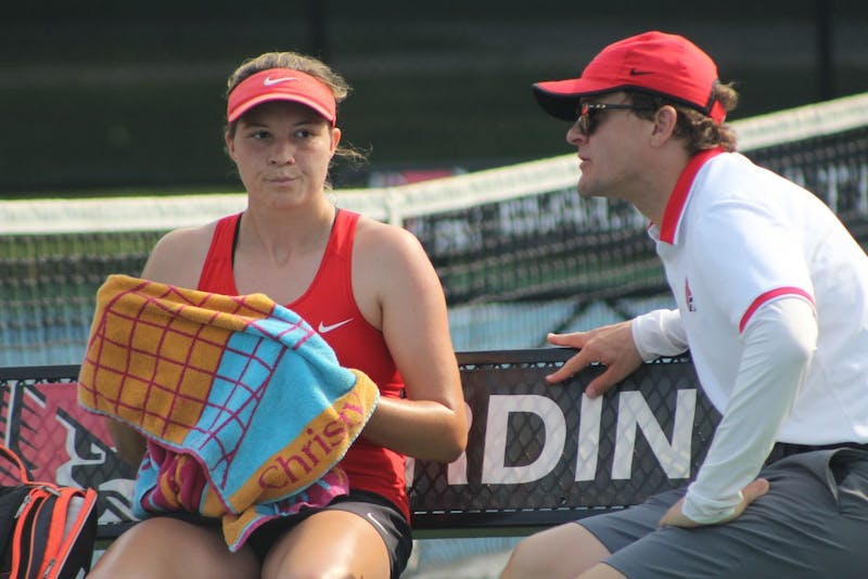 Junior Rebecca Herrington and head coach Max Norris talk to each other a her singles match against Detroit Mercy on the first day of the Hidden Dual tournament. Herrington won her first set, 6-2. Photo by Patrick Murphy