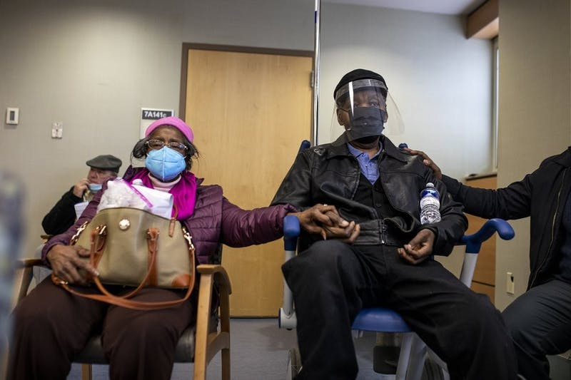 FILE - In this Jan. 23, 2021, file photo, Dorothy Kade, left, holds the hand of her husband, Walter Kade Jr., as they wait in the observation room after he received a COVID-19 vaccine at the VA Medical Center, in Philadelphia. (Tyger Williams/The Philadelphia Inquirer via AP, File)