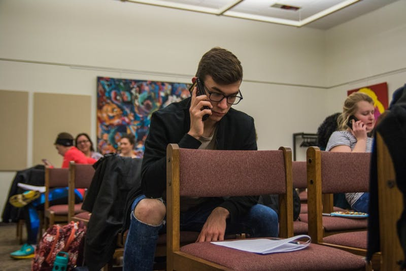 Ben Slightom, junior architecture and philosophy major, was one of many students gathered in Bracken Library on Jan. 30 to call U.S. and state senators and representatives, urging them to stop Indiana's SB 285, the Devos Confirmation, the ACA Repeal and to reject the Muslim ban. Reagan Allen // DN