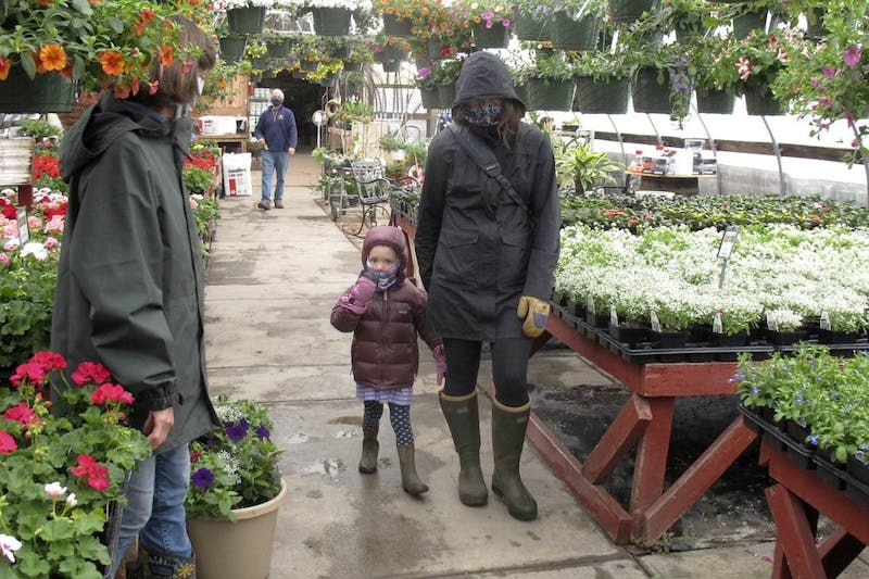 Kim and 4-year-old Marley Farwell, of Stowe, Vt., walk through the greenhouse at Evergreen Gardens of Vermont April 27, 2020, in Waterbury Center, Vt. Monday was the the first day businesses such as greenhouses and garden centers could allow a small number of customers inside as part of Vermont's gradual coronavirus pandemic reopening plan. (AP Photo/Wilson Ring)