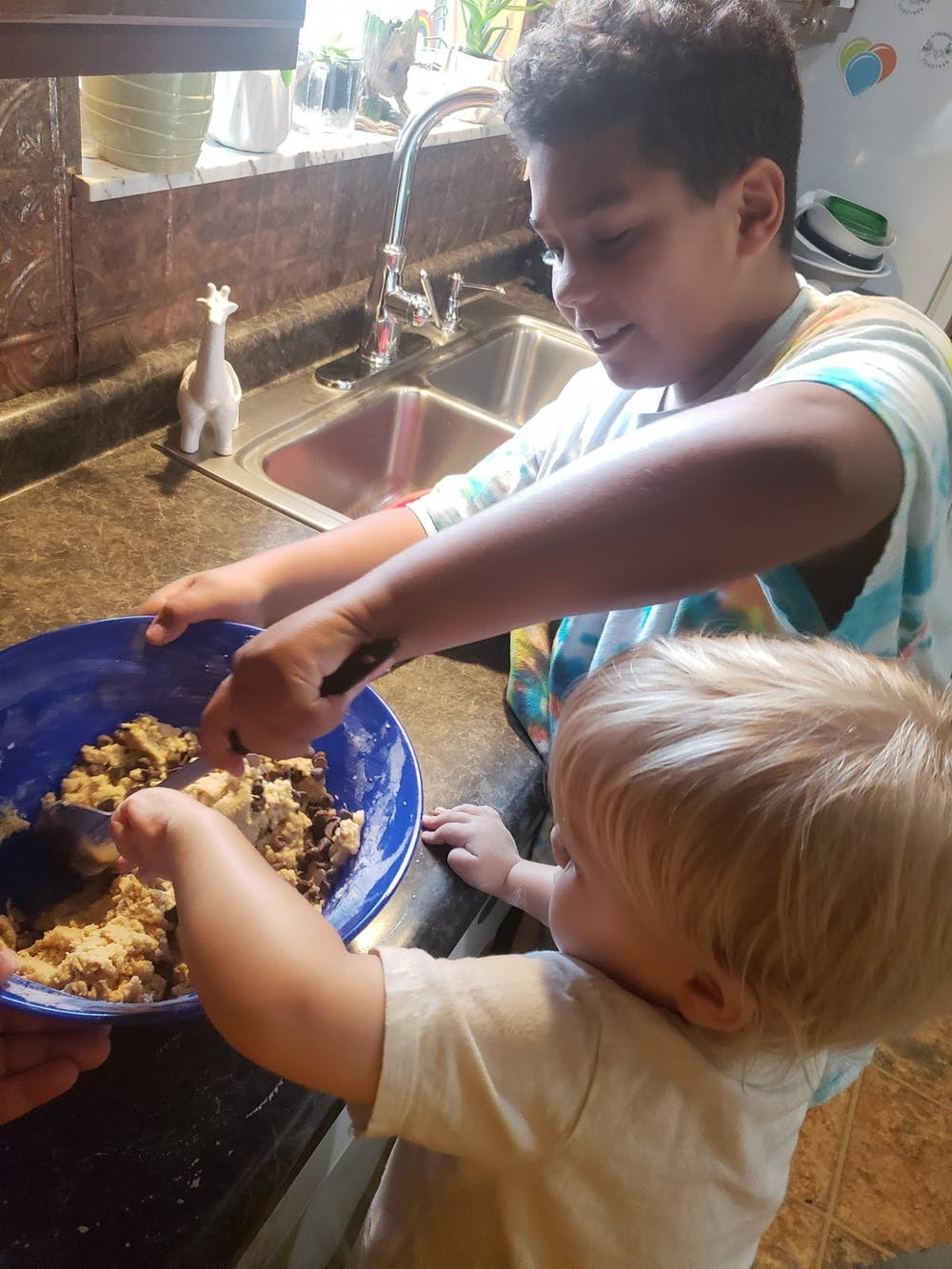 Karin Hartwell's children, Shawn (left) and Ki (right) Hartwell help her bake this summer in their kitchen. Hartwell said Shawn and Ki only help make desserts when they're for their family, not her customers, for hygienic purposes. Karin Hartwell, Photo Provided