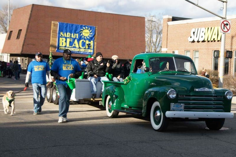 Sarah Beach, city council candidate, and her fellow attendants walk down walnut street during the St. Patrick's Day Parade March 16, 2019. All of the parade entries shared three common interests: old-fashioned vehicles, pets and the color green. Kamryn Tomlinson, DN.