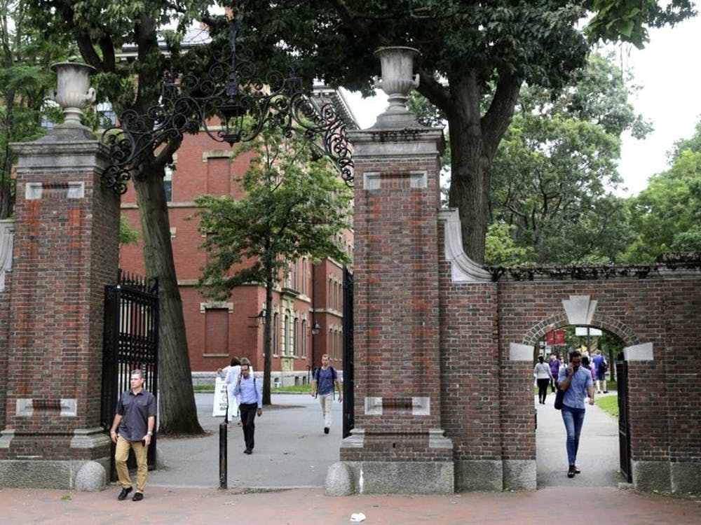 Pedestrians walk through the gates of Harvard Yard at Harvard University Aug. 13, 2019, in Cambridge, Mass. Harvard and Massachusetts Institute of Technology filed a federal lawsuit July 8, 2020, challenging the decision to bar international students from staying in the U.S. if they take classes entirely online this fall. (AP Photo/Charles Krupa, File)