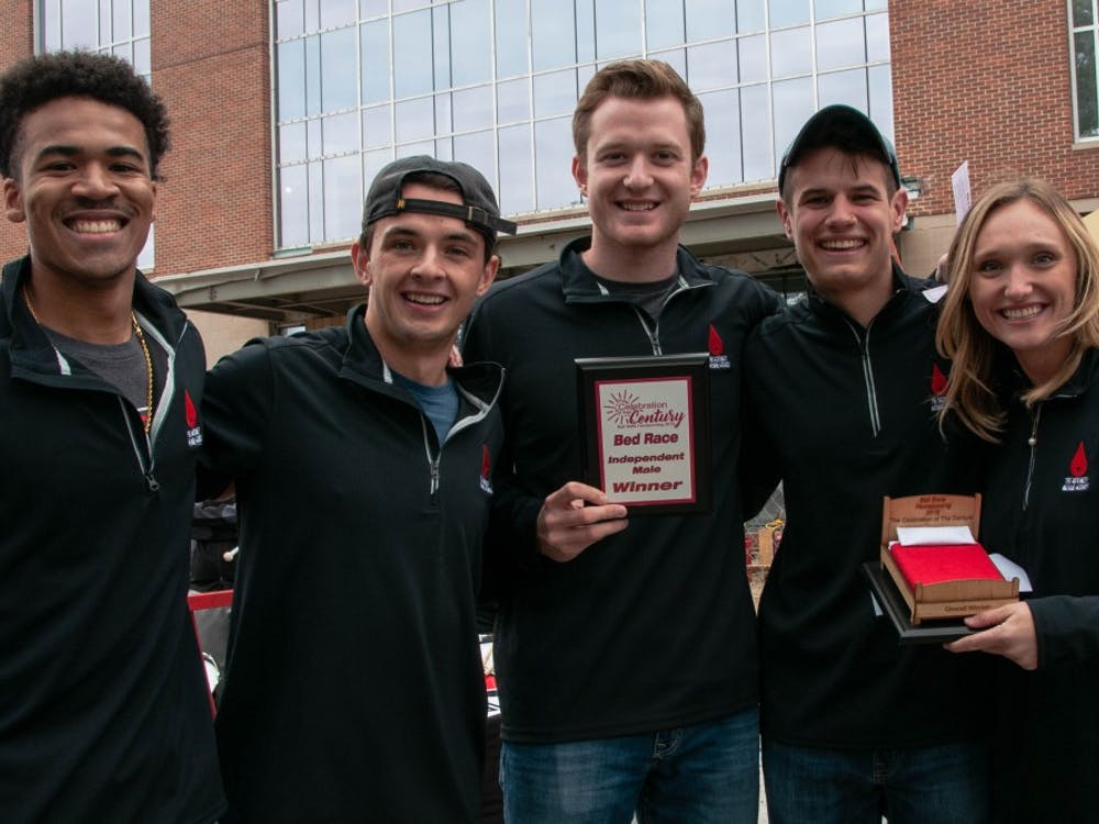 McKinley Avenue Agency pose with their plaque after competing in the Bed Race, an annual Homecoming event Oct. 19, 2018, on Riverside Ave. The team earned their title for having the fastest time in the independent male category. Madeline Grosh,DN