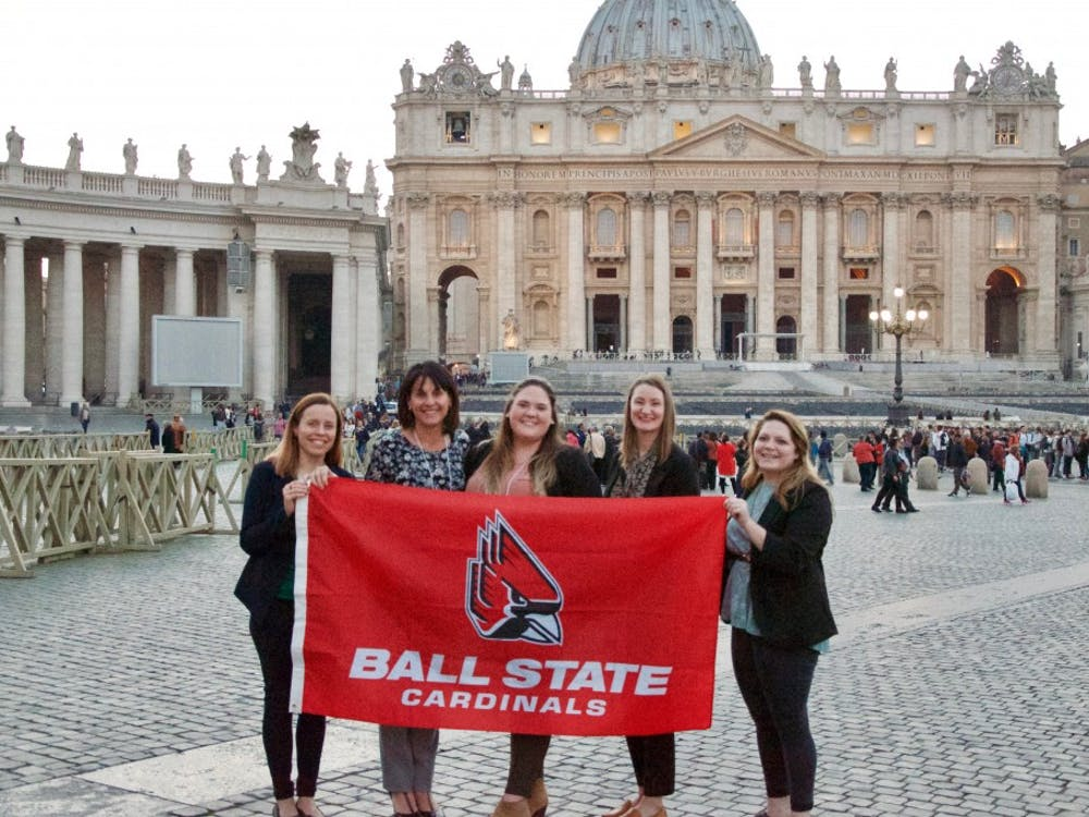 Aiste Manfredini, Dr. Jennifer Palilonis, BriAnna Eikenberry, Sarah Janssen and Jessica Pettengill hold a Ball State flag during their visit to Rome.