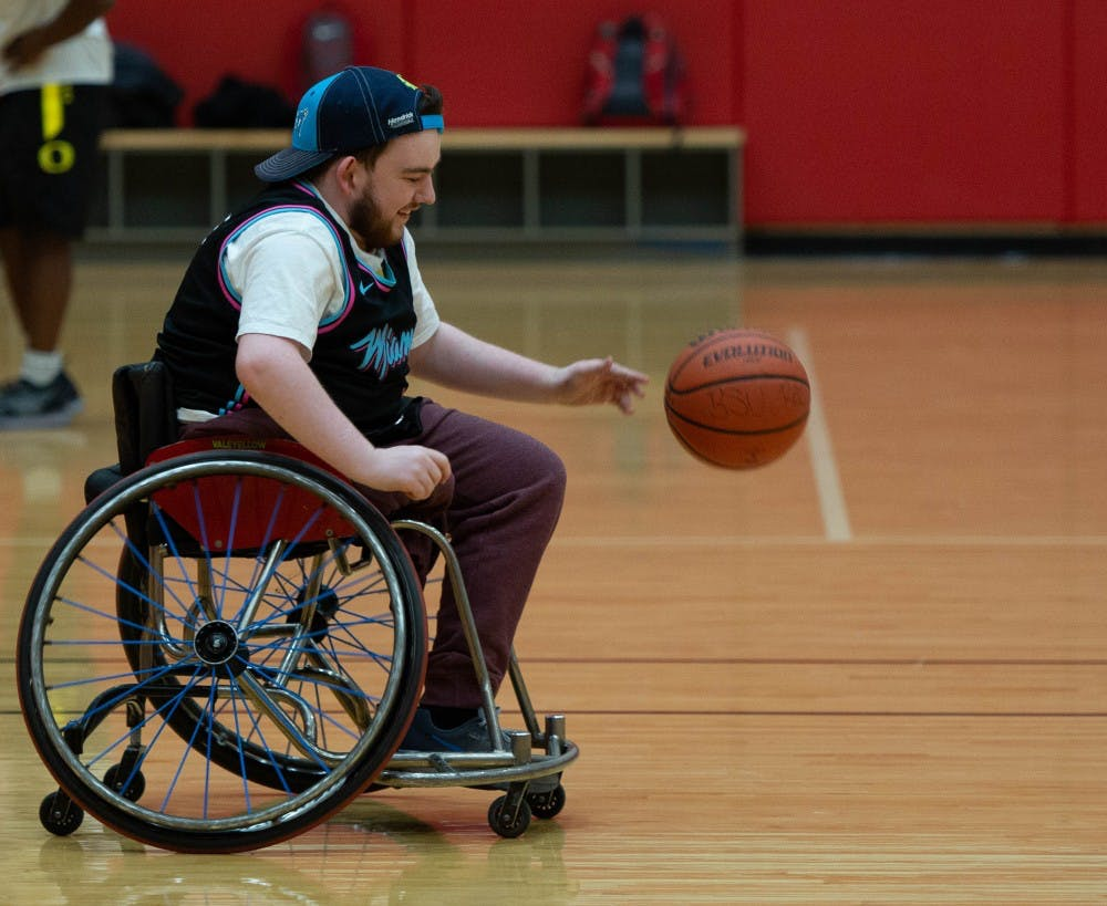 Aaron Gillen, junior exchange student, smiles as he moves the ball upcourt March 27, 2019 in the Student Receration and Wellness Center. The group is attempting to make wheelchair basketball into a club sport. Scott Fleener, DN