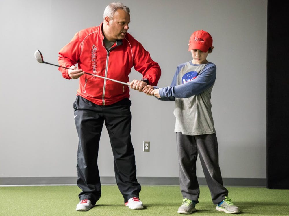 Ball State men's golf head coach Mike Fleck works with Manasseh Crum on his swing Jan. 23 at the Travis Smith Short Game Center. Crum has Polyarticular Juvenile Idiopathic Arthritis. He is part of Team IMPACT, a national non-profit organization that connects children facing serious or chronic illnesses with college athletic teams. Rachel Ellis, DN