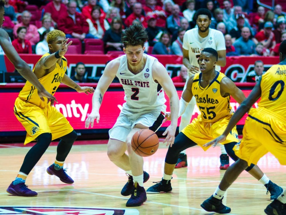 Junior guard Tayler Persons, surrounded by his opponents, makes an effort to get the ball out of the circle and into the basket during the game against Kent State at John E. Worthen Arena Feb. 9. Ball State's men's basketball team defeated Kent State 87 - 68. Stephanie Amador, DN