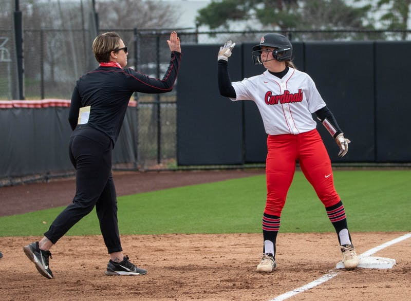 Head coach Lacy Wood celebrates with sophomore infielder Haley Wynn after a hit that got three runners to home March 26, 2021, at the Softball Field at First Merchants Ballpark Complex. The Cardinals won 8-6 against the Falcons. Jaden Whiteman, DN