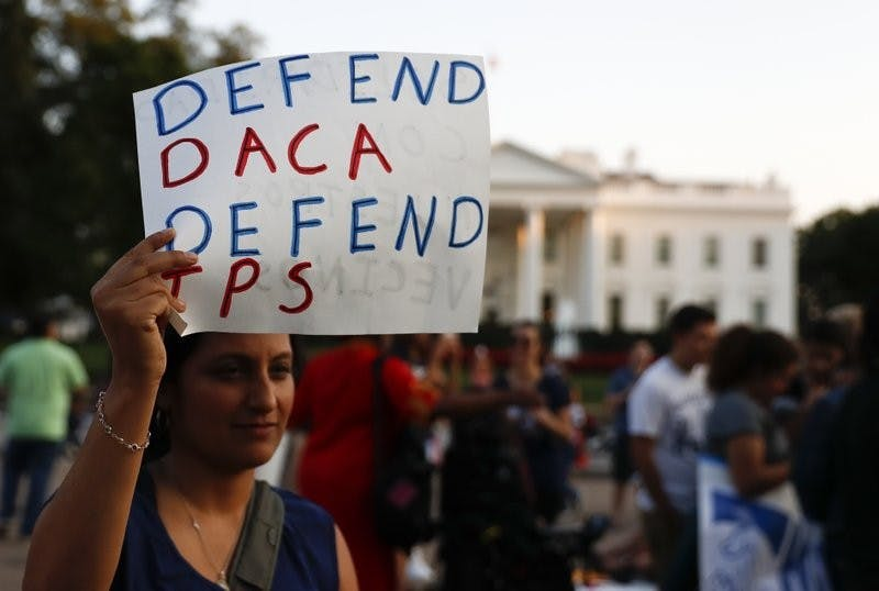"A woman holds up a sign that reads ""Defend DACA Defend TPS"" during a rally supporting Deferred Action for Childhood Arrivals, or DACA, outside the White House in Washington, Monday, Sept. 4, 2017. AP Photo/Carolyn Kaster, Photo Provided"