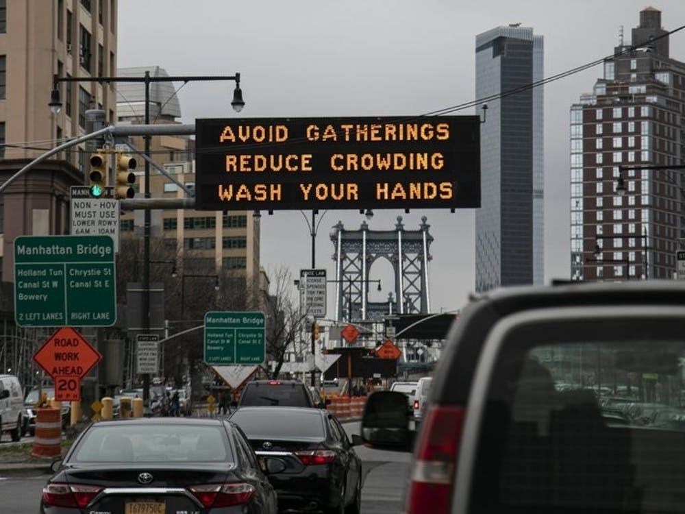 In this March 19, 2020, file photo, the Manhattan bridge is seen in the background of a flashing sign urging commuters to avoid gatherings, reduce crowding and to wash hands in the Brooklyn borough of New York. The coronavirus pandemic is leading to information overload for many people, often making it difficult to separate fact from fiction and rumor from deliberate efforts to mislead. (AP Photo/Wong Maye-E, File)