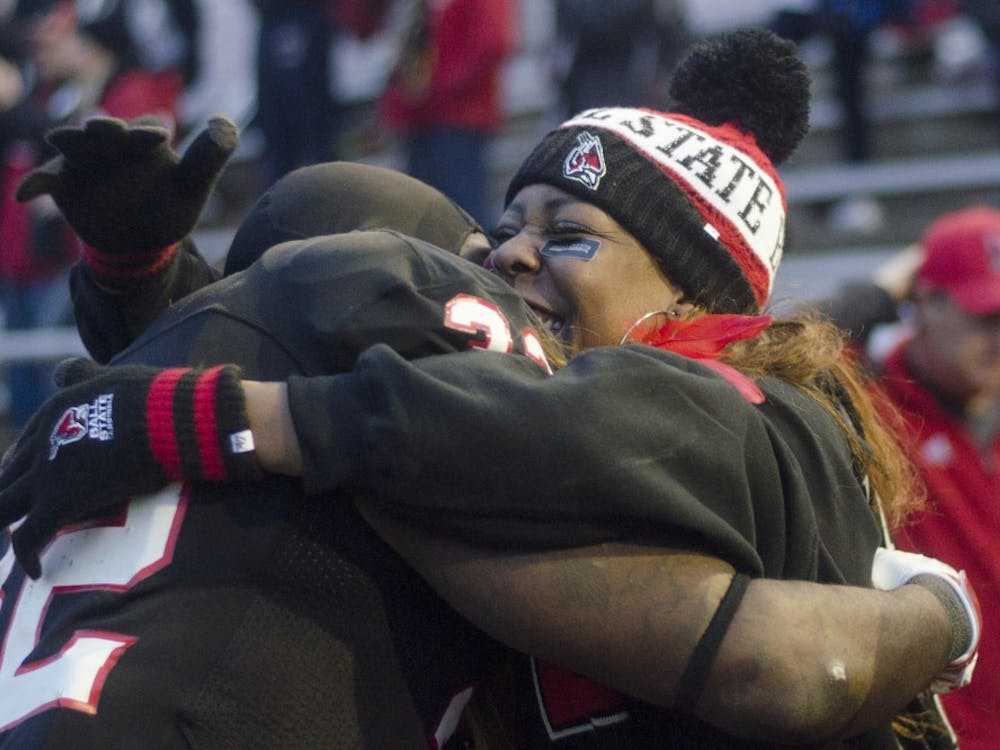 Senior running back Jahwan Edwards hugs a family member after the game against Eastern Michigan on Nov. 22 at Scheumann Stadium. DN PHOTO BREANNA DAUGHERTY