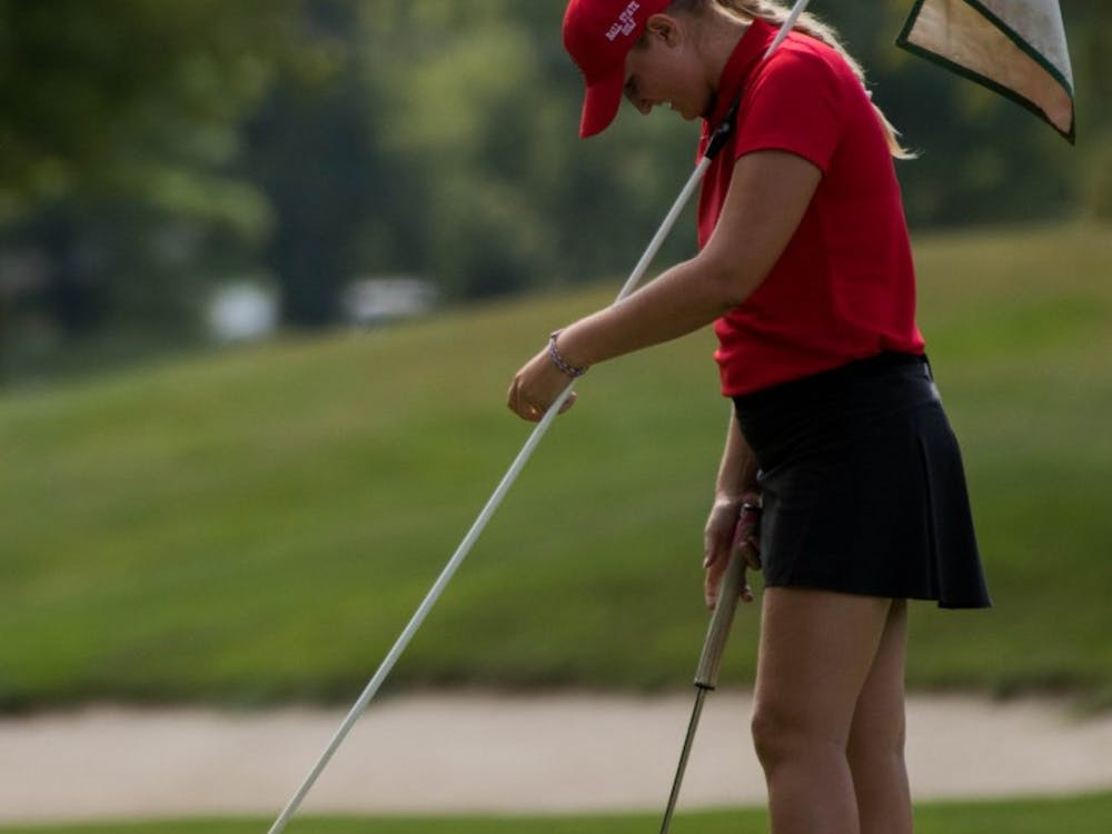 Freshman Dylann Armstrong holds the flag on the green as her opponents putt in their balls Sept. 17, 2018, at the Players Club in Yorktown, Indiana during the Cardinal Classic Golf Tournament. The Cardinals faced off against 16 other colleges in the two-day tournament. Eric Pritchett,DN