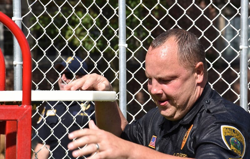 Sergeant Scott Stafford climbs back up on the bench after falling into the water tank. The Dunk-a-Cop fundraiser's goal was to give back to the community and create dialogue with students. Patrick Calvert // DN