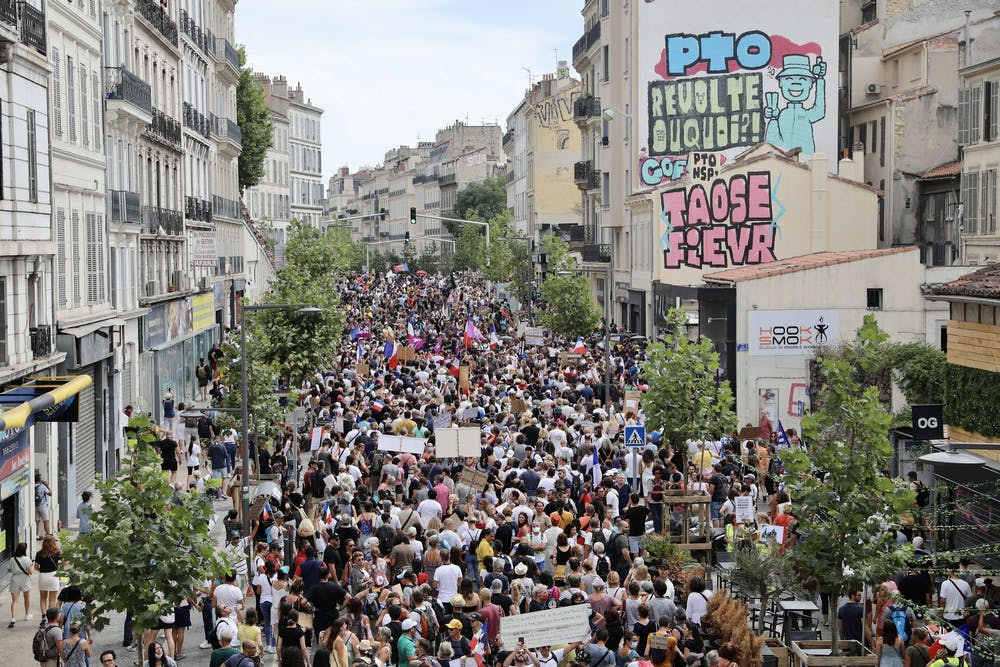 ProtestErs hold up banners and placards during a nationwide protest against France's new COVID-19 health pass on Aug. 7, 2021, in Marseille, France. (Roger Anis/Getty Images/TNS)
