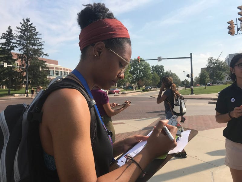 "Melissa Booth, sophomore fashion merchandising major, answering the question, ""How do we achieve a more peaceful future?"" on a paper square for #WordsMatterBSU Sept. 21 at the Scramble Light. Booth said understanding people's different perspectives will allow people to ""mutually coexist"" in response to the question. Hannah Gunnell, DN"
