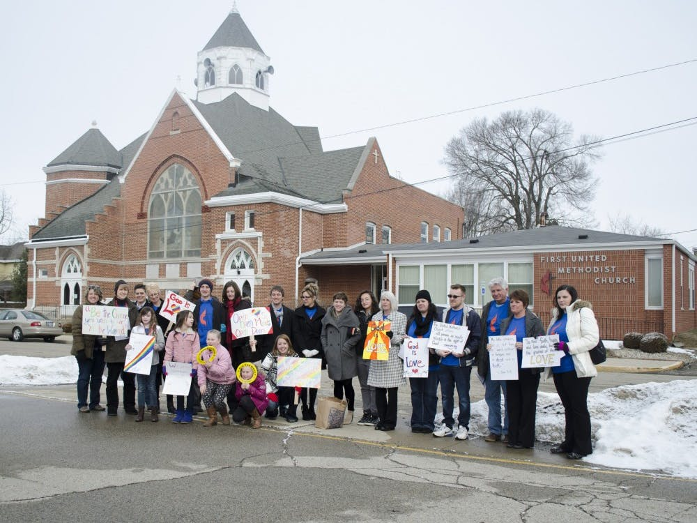 A group of protesters stand outside of the First Methodist Church of Alexandria before starting the protest on Sunday. DN PHOTO BREANNA DAUGHERTY