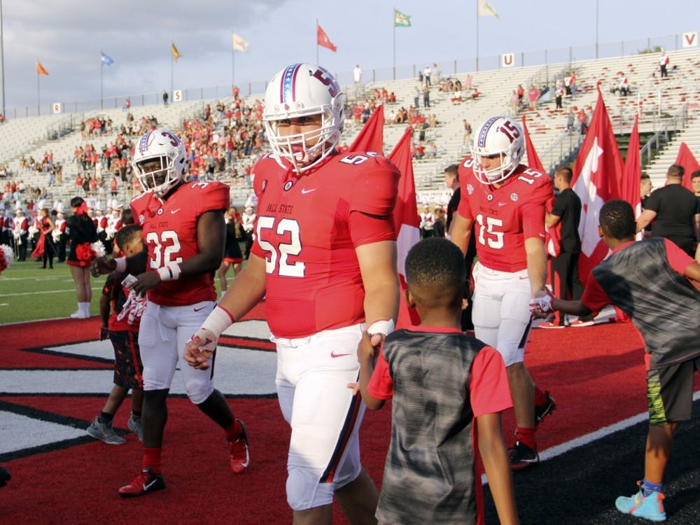 Ball State Football captains redshirt senior Jeremiah Jackson (32), redshirt senior Fred Schroeder (52) and redshirt junior Riley Neal (15) high five a young Ball State fan before the coin toss for the Cardinals' game against Central Connecticut State Thursday, Aug. 30, 2018, at Scheumann Stadium. Paige Grider, DN