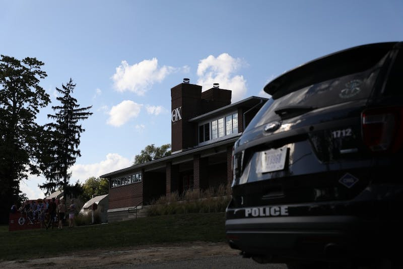 Theta Chi members and friends sit outside their fraternity house Oct. 3, 2018. The Muncie Police Department sit in the driveway monitoring the house and its residents. Rebecca Slezak, DN