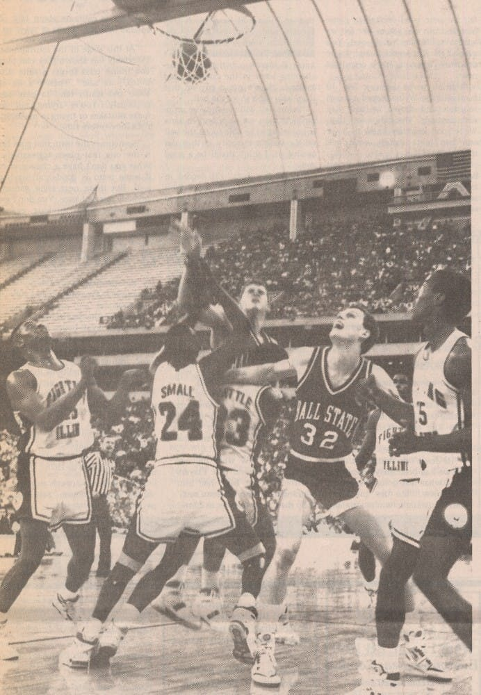 Greg Miller puts up a shot as Roman Muller fights for rebounding position in a 1989 game. Miller and Muller were two of nine seniors on the 1990 team that went to the Sweet 16. This photo was printed in the March 21, 1989 Daily News edition.