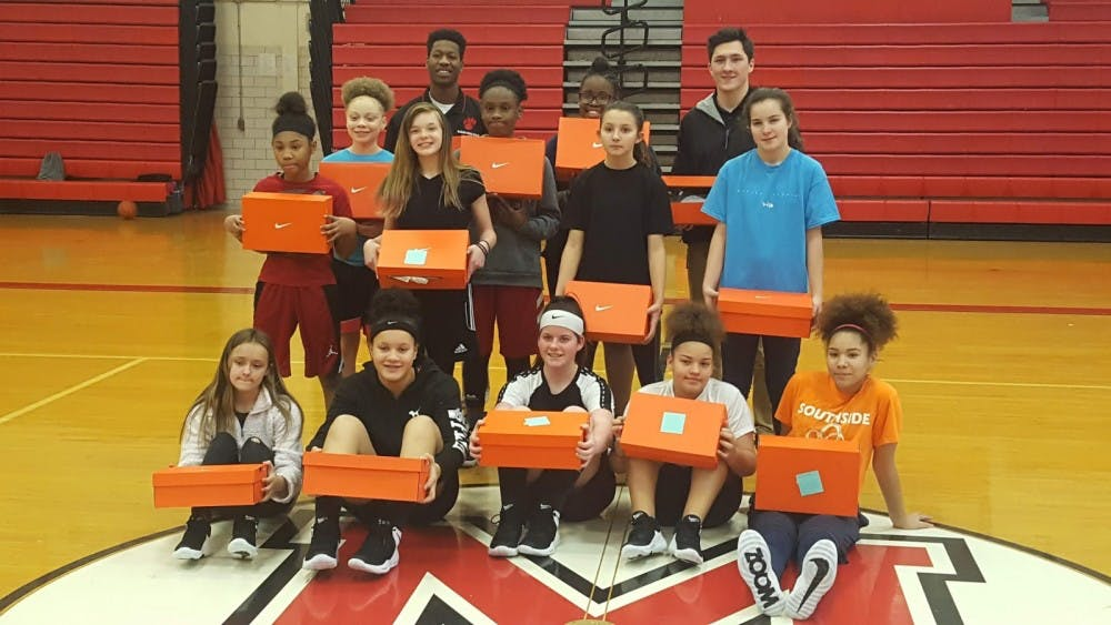 Seventh and eighth grade girls basketball teams at Southside Middle School pose with their new shows with assistant head coach Jaleel Pryuer (left) and head coach Erik Hoglund. The Interfraternity Council donated $1,500 to both programs to purchase new shoes for the season. Evan Weaver, DN