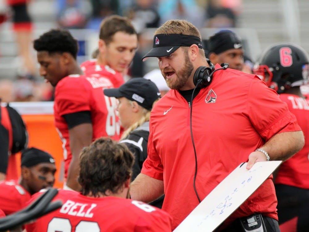 Offensive line coach Kyle DeVan goes over a play during the Cardinals' game against Northern Illinois on Oct. 1 in Scheumann Stadium. Ball State lost 31 to 24. Paige Grider// DN