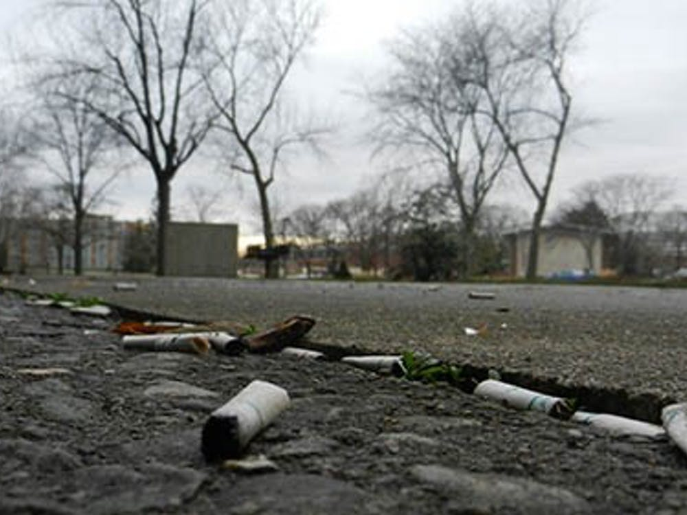 Cigarette buds scatter the ground at the smoking area by the Studebaker East Complex. The new ban will force the students, faculty and staff who use this area to move off campus to smoke. DN FILE PHOTO EMMA FLYNN