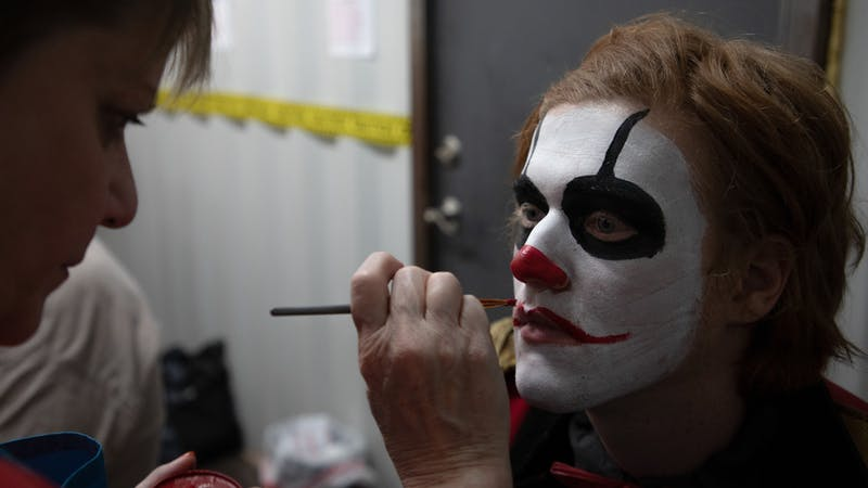 Jodie Morgan, the manager of Indy Scream Park's makeup trailer, works on painting lips onto a Midway actor's face for their costume. Indy Scream Park's makeup artists work for two hours each day before the park opens to complete the actor's full look. Jacob Musselman, DN